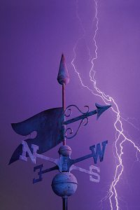 Tip of weather vane against purple sky with lightning bolt