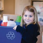 Young girl holding recycle bin full of plastic bottles and cardboard